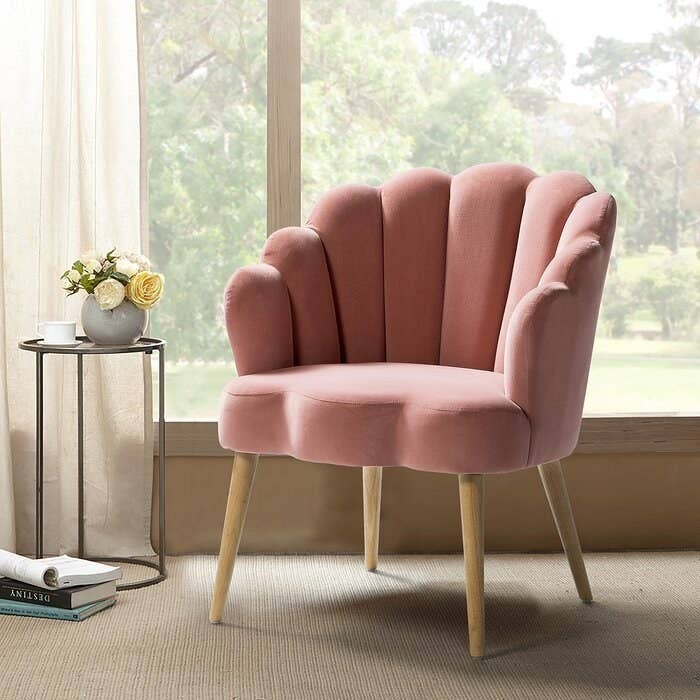pink clamshell velvet chair with wooden legs