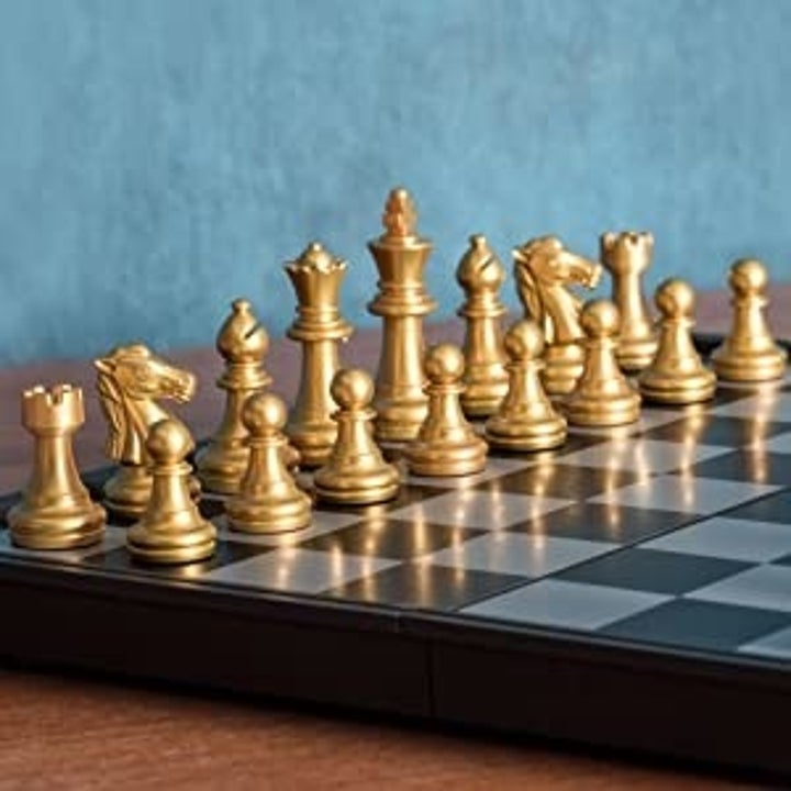 A close up of the golden-colored chess set.