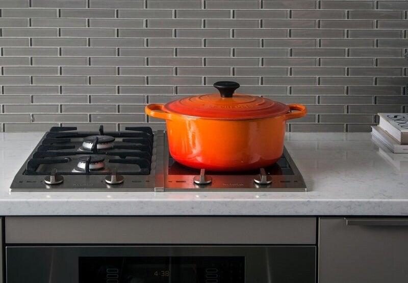 An orange Le Creuset dutch oven in orange on a stovetop