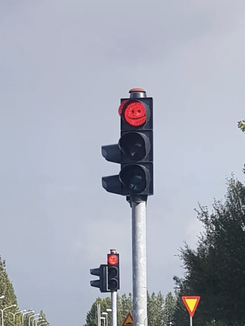 Graffiti on a stop light makes it look like it is smiling