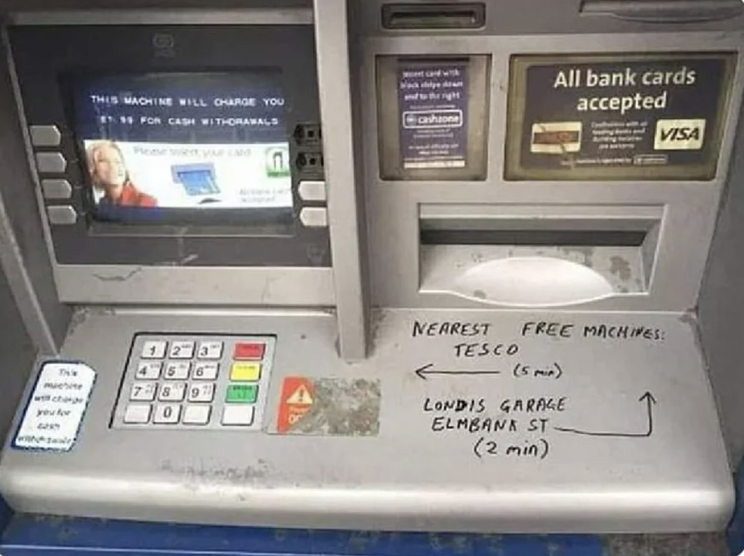 Graffiti on an ATM points people toward the closest ATM that doesn't charge an additional fee