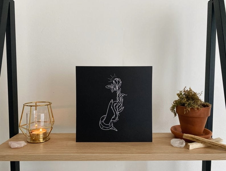 a print of a hand holding a snake and rose on a black background