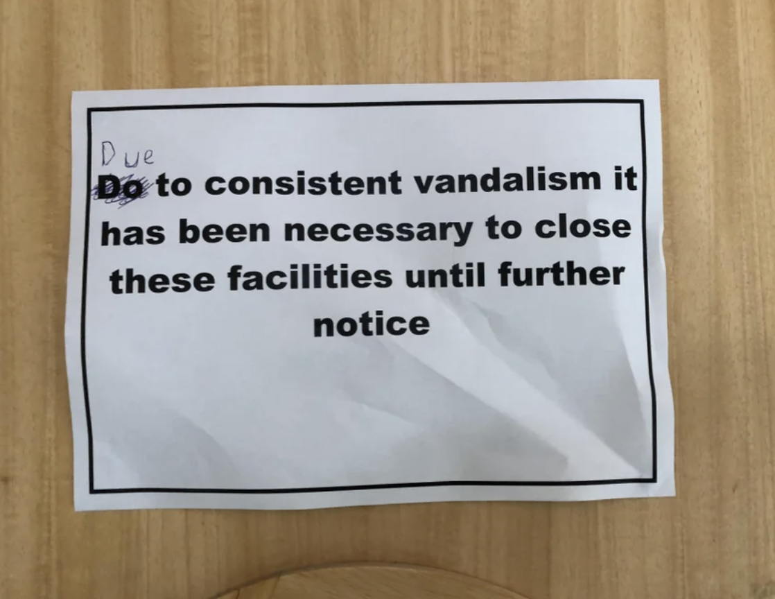 A sign saying a bathroom is closed due to consistent vandalism has been written on, correcting its grammar