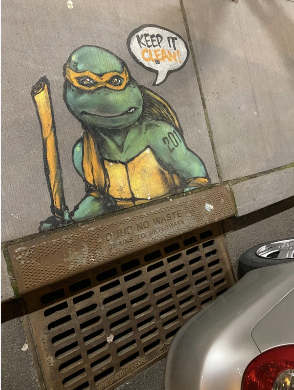 A drawing of a teenage mutant ninja turtle looms over a sewage dump