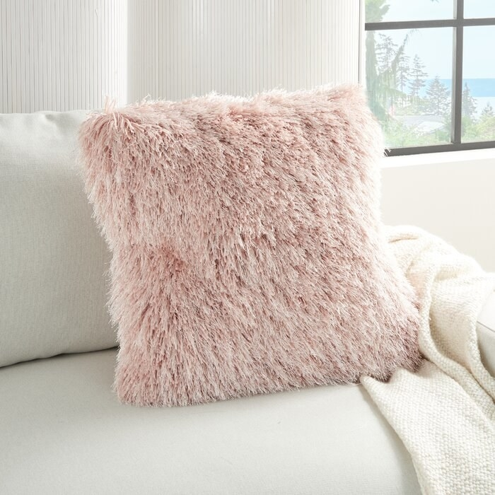pink fuzzy throw pillow on a white couch