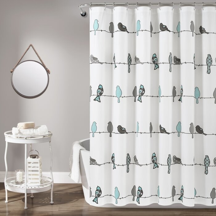 white shower curtain with blue and gray birds sitting on a wire