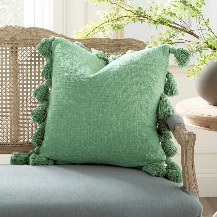 green throw pillow with a thick tassel border