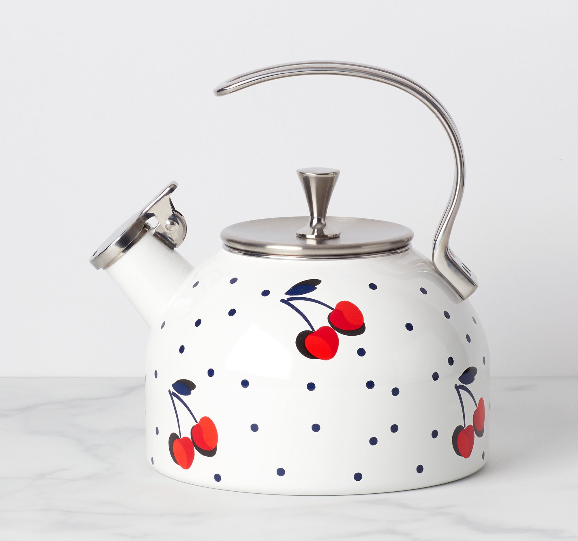 the tea kettle is white with cherries and black dots on it