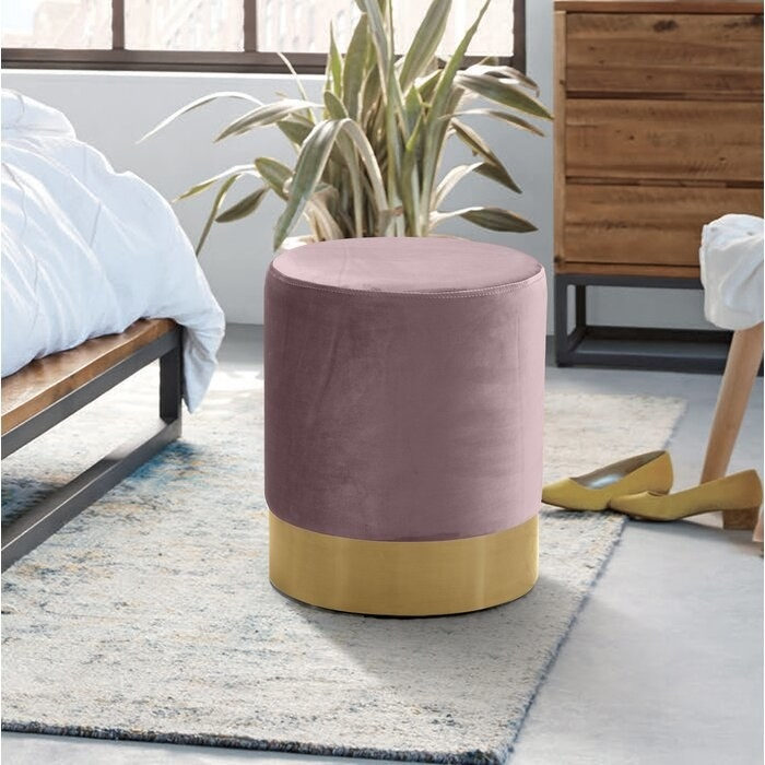 pink ottoman with a gold bottom