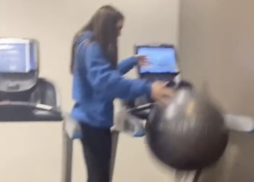 A woman stands on a treadmill with an exercise ball