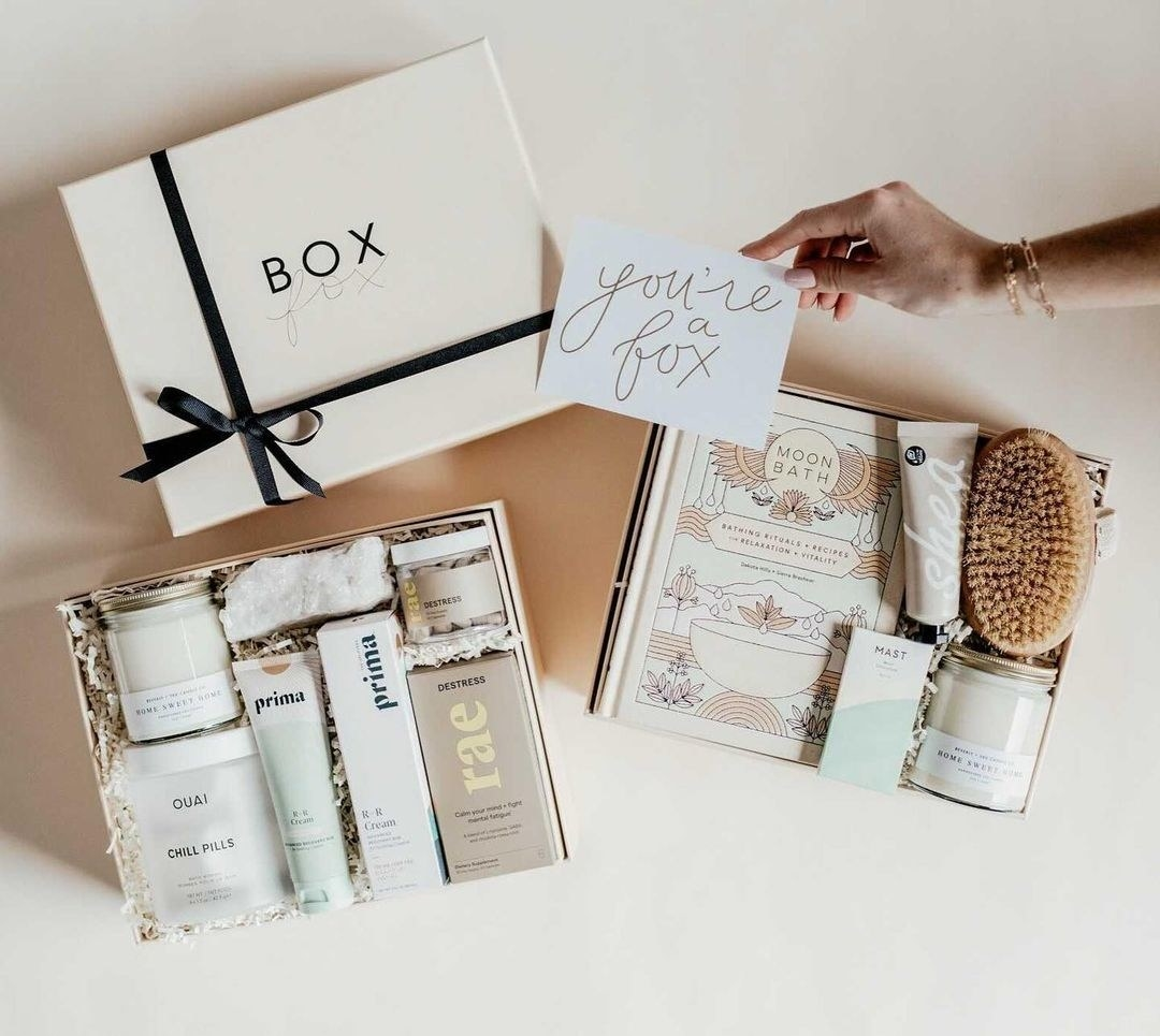 """A hand holding a card that reads """"you're a fox"""" next to two gift boxes filled with skincare, books, candles and more"""