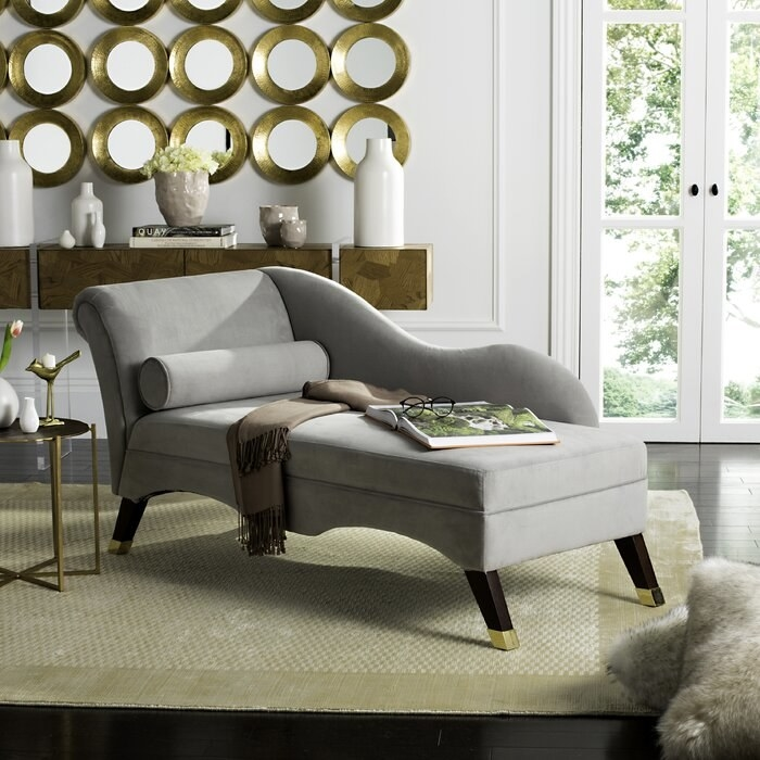 gray lounge chair with blanket, book, and glasses on it