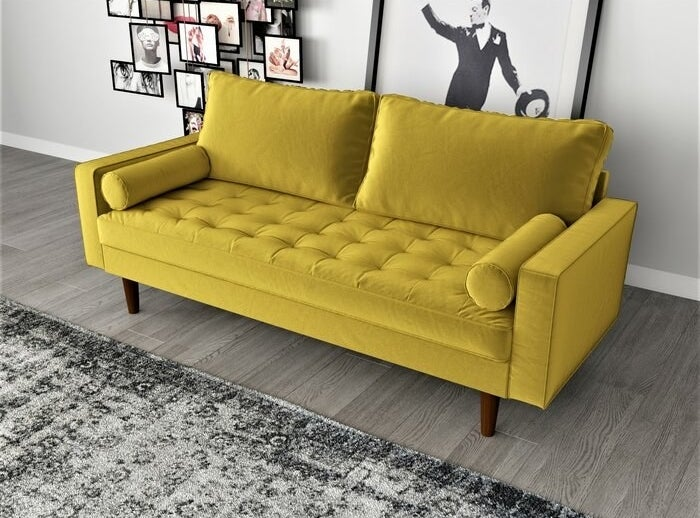 a yellow velvet couch sitting in a living room