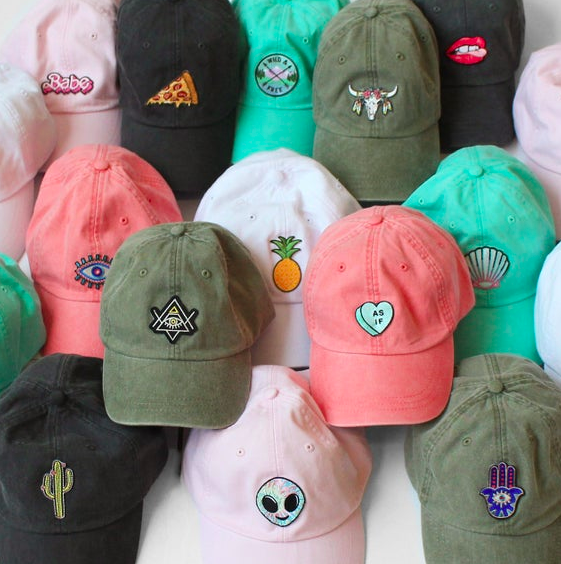 Pink, black, and green baseball caps with different patches on the front