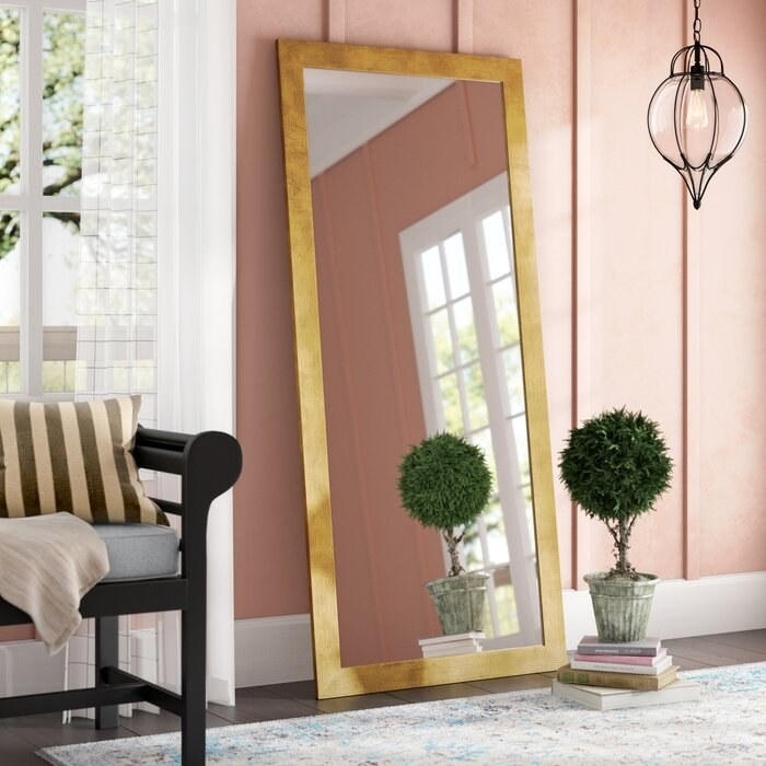gold framed full length mirror leaning against a pink wall