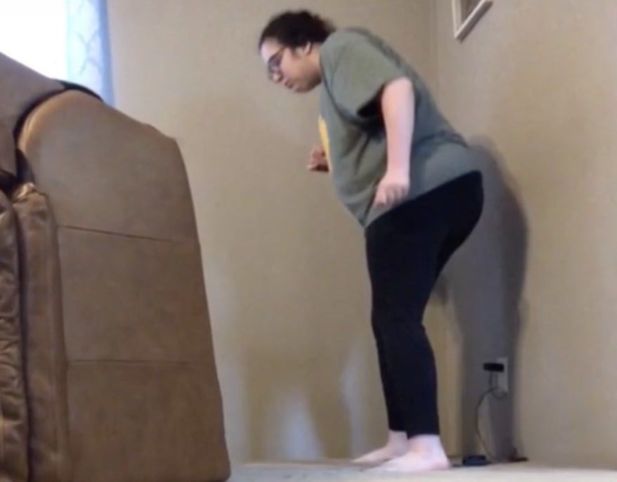 A woman looks under her living room chair for something