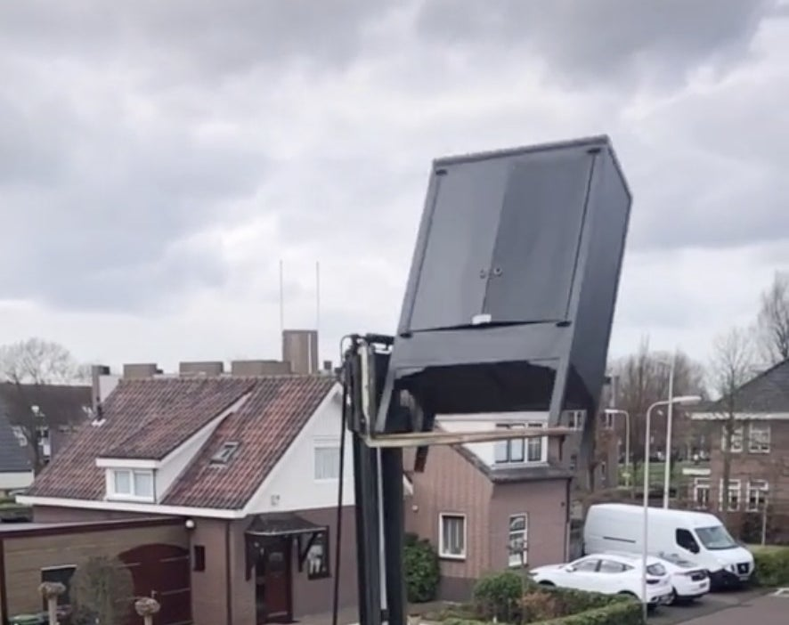 A dresser begins to fall off of a forklift while high in the air