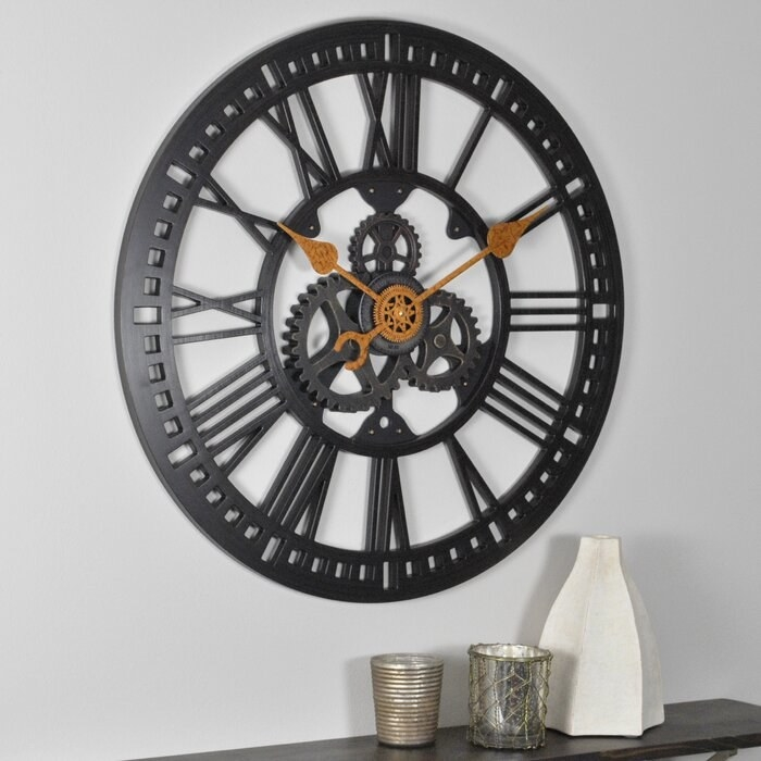 black gear-style wall clock hanging on the wall