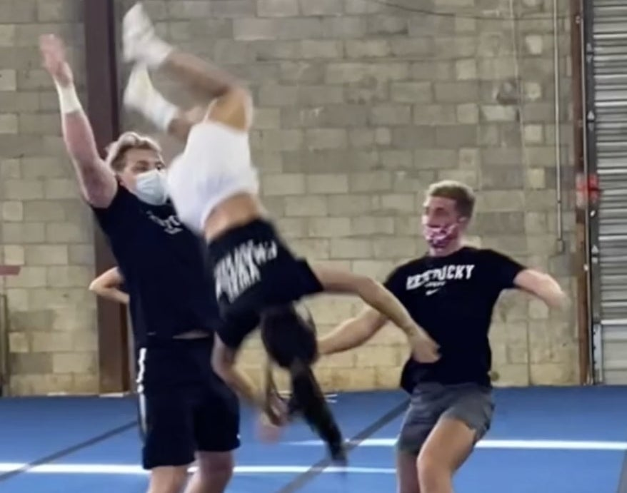 A cheerleaders flies through the air after two men fail to catch her