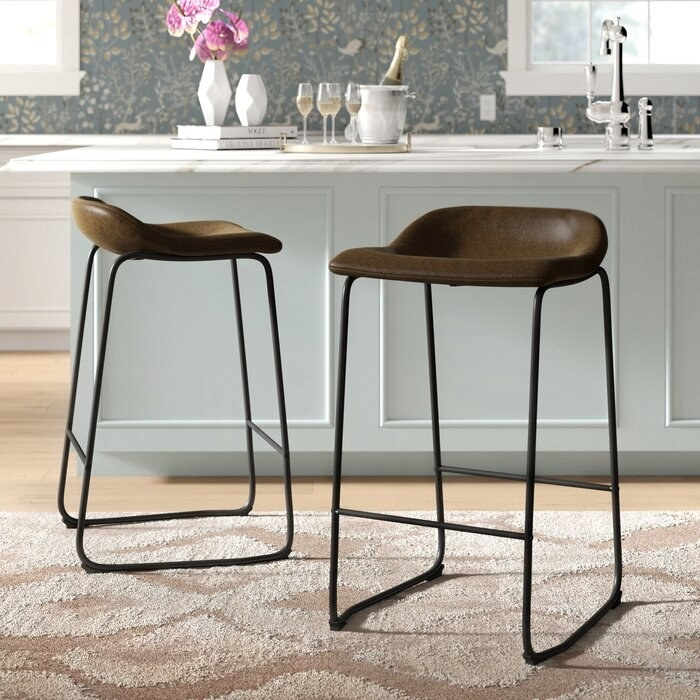 two stools with brown faux leather seats and black legs