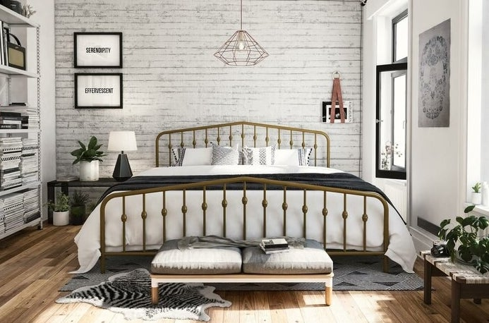 gold platform bed in a bedroom with white linens on top