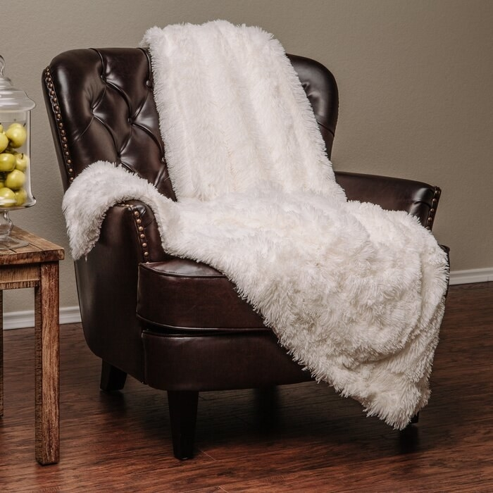white shaggy blanket thrown across a leather arm chair