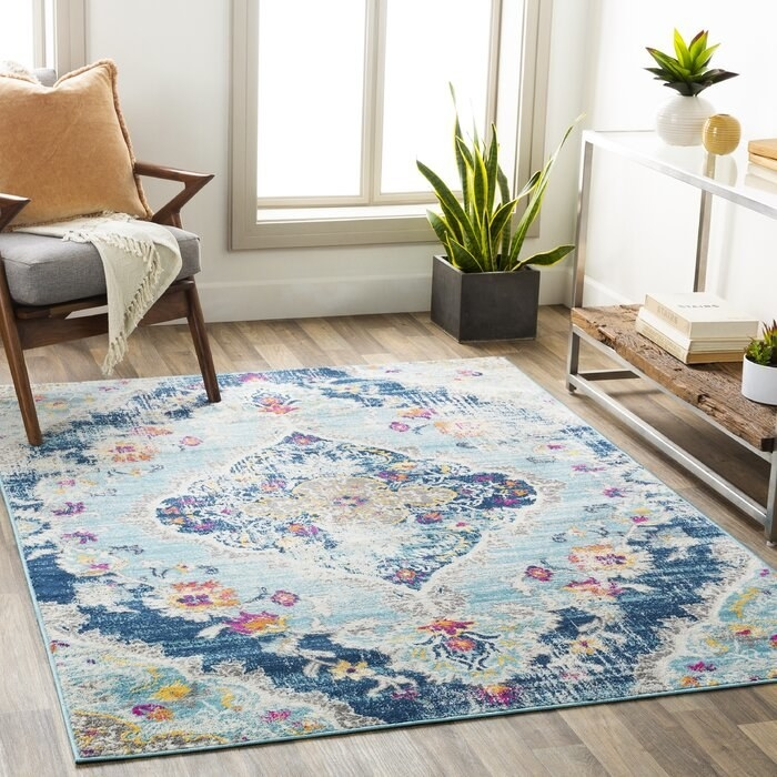 blue area rug in the middle of a living room