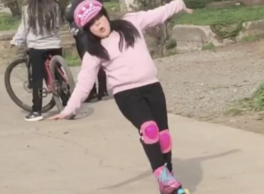 A little girl is about to fall while roller skating