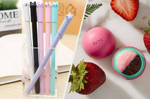A glass jar filled with six pens that have cat faces on the lids, A small eos lip balm container that's open with strawberries surrounding it