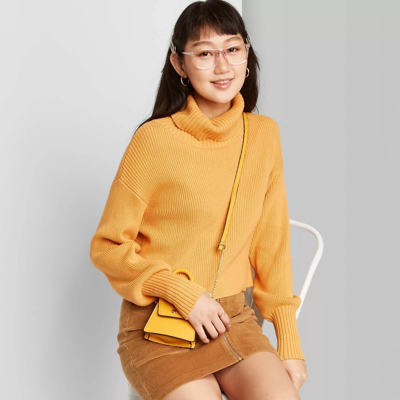 Model wears mustard yellow cropped turtleneck sweater with a suede skirt and a micro yellow bag