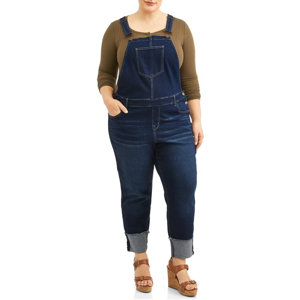 model wears dark wash cuffed overalls