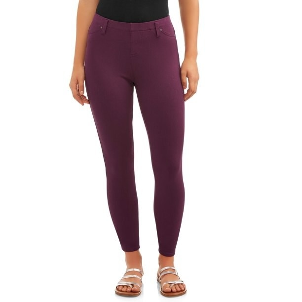 model wears burgundy colored jeggings