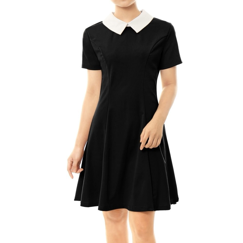 model wears black doll collared dress