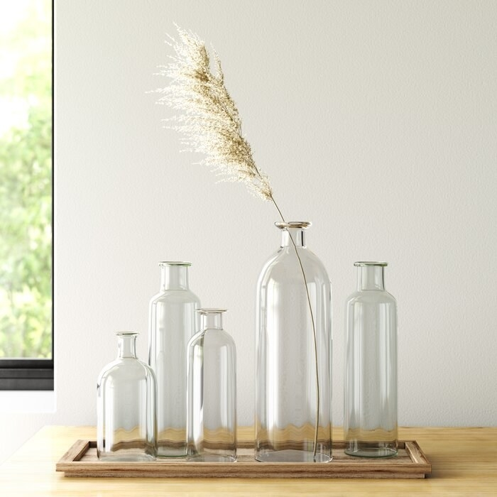 five clear skinny vases with a weed in one of them