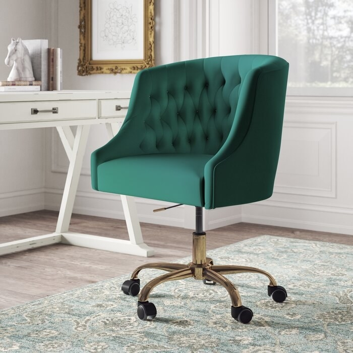 Green tufted back desk chair with wheels on the bottom