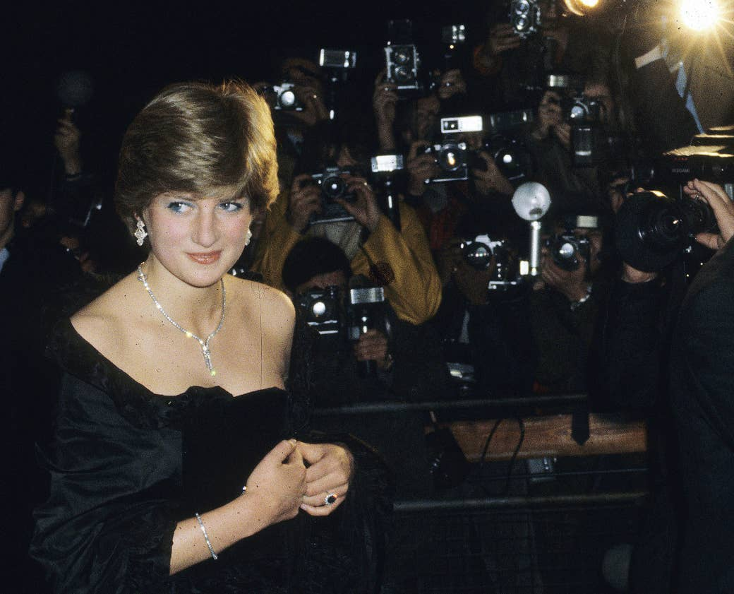Princess Diana in front of a wall of paparazzi photographers