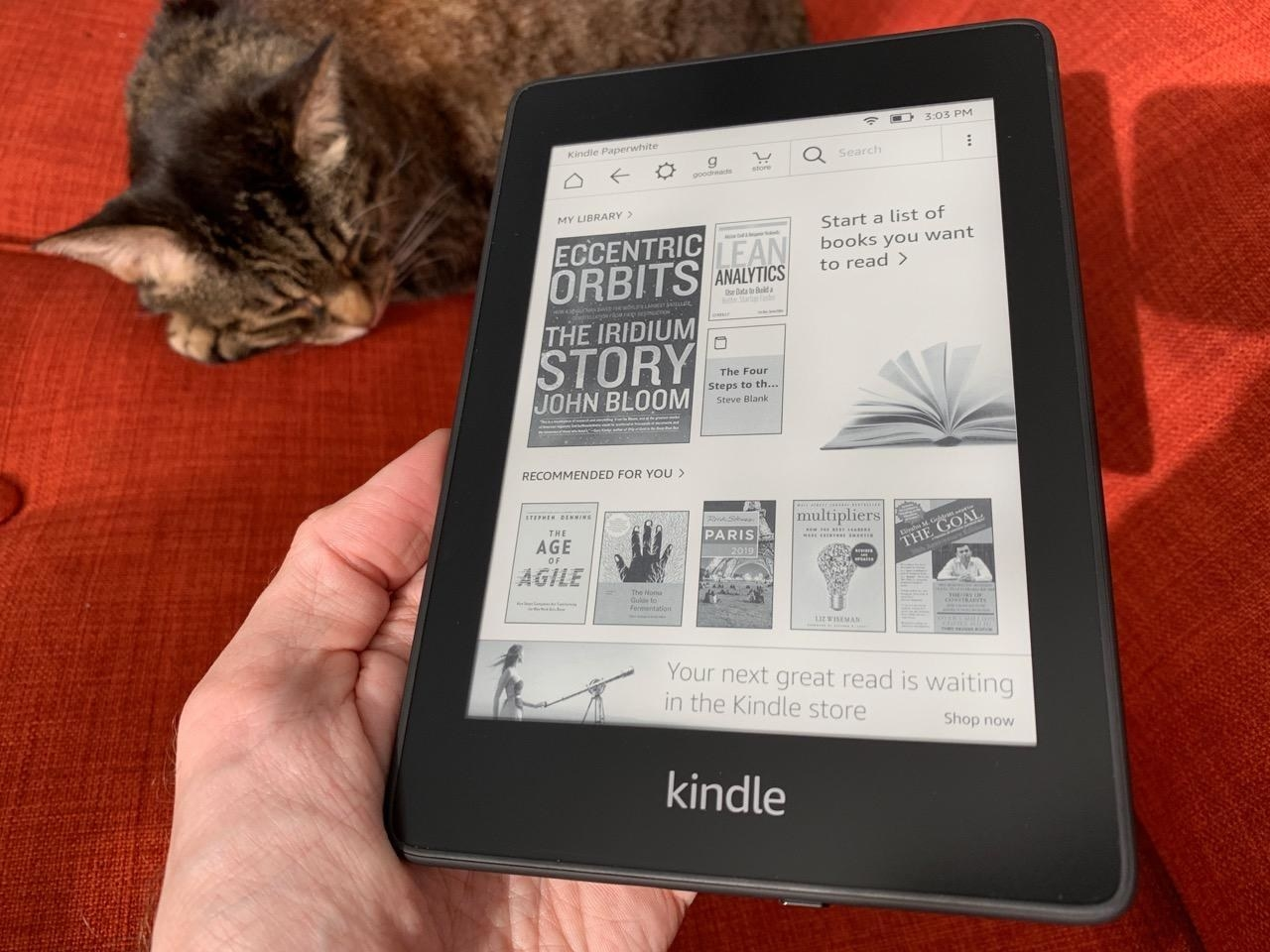 A reviewer holding the Kindle which is open to the black-and-white home screen
