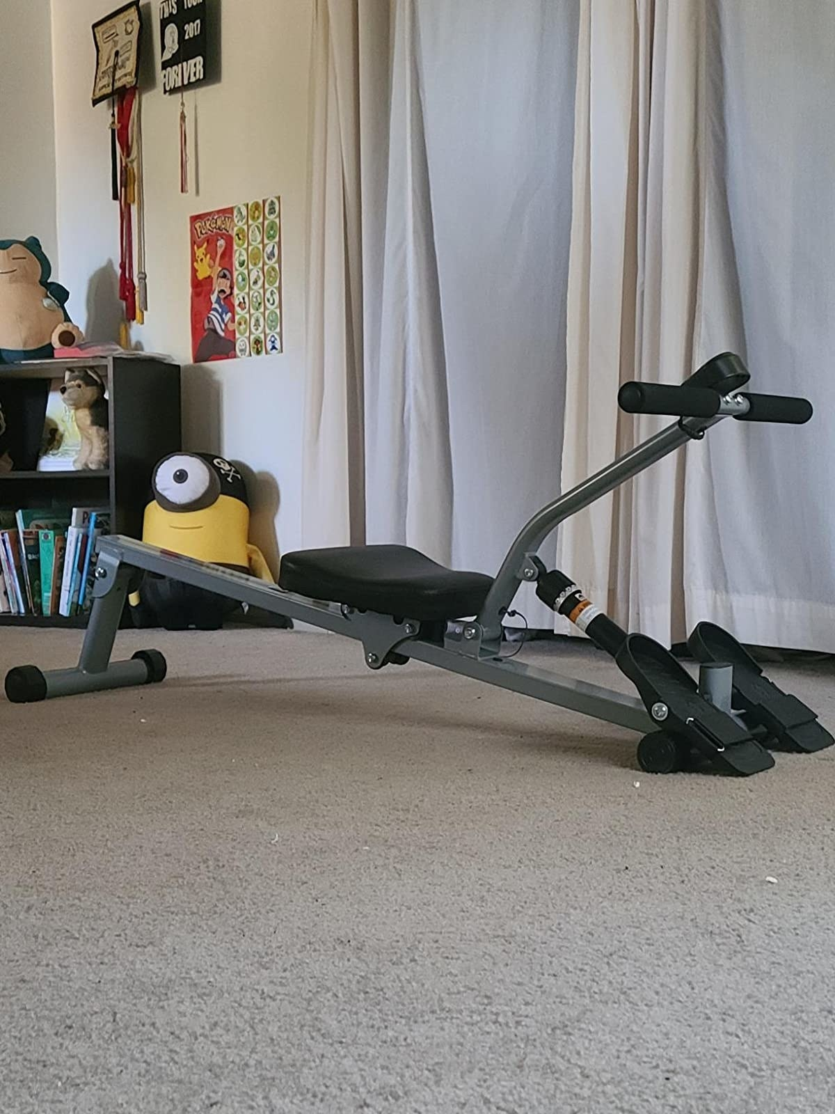 Reviewer pic of the small rowing machine in dark grey with black seat, food holders, and arm rest