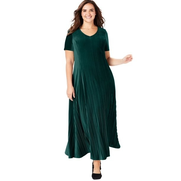 model wears emerald green pleated dress