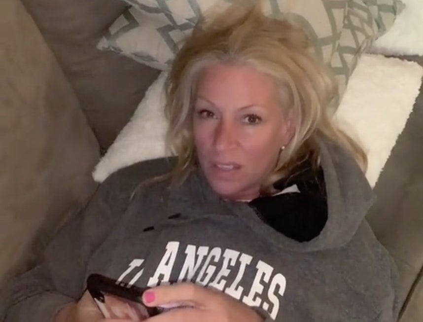 A mom makes a sassy face while lying on the couch