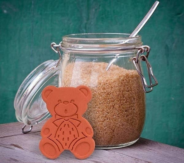 The brown sugar bear outside of a jar of brown sugar