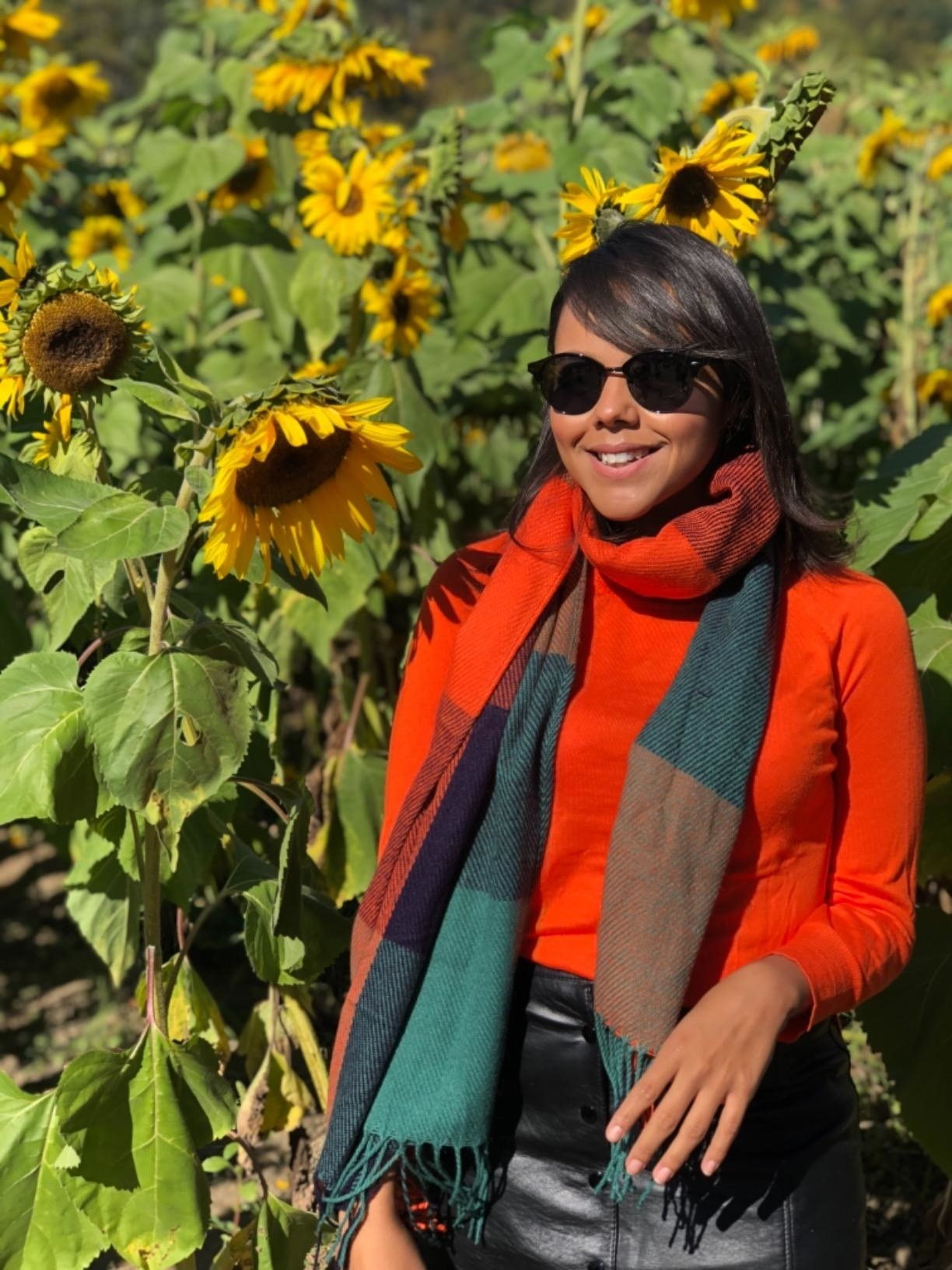 Reviewer wears color block scarf with bright red turtleneck top and a black skirt