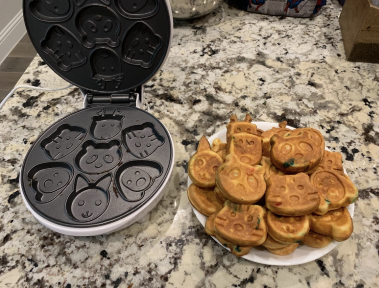 Reviewer photo of animal waffle maker next to completed animal waffles on a plate