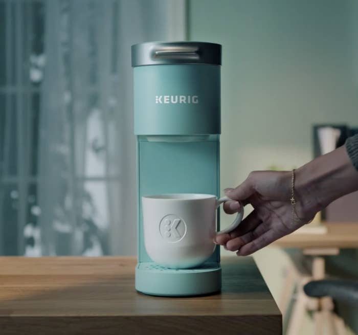 Person is holding a cup on a mint blue single cup Keurig