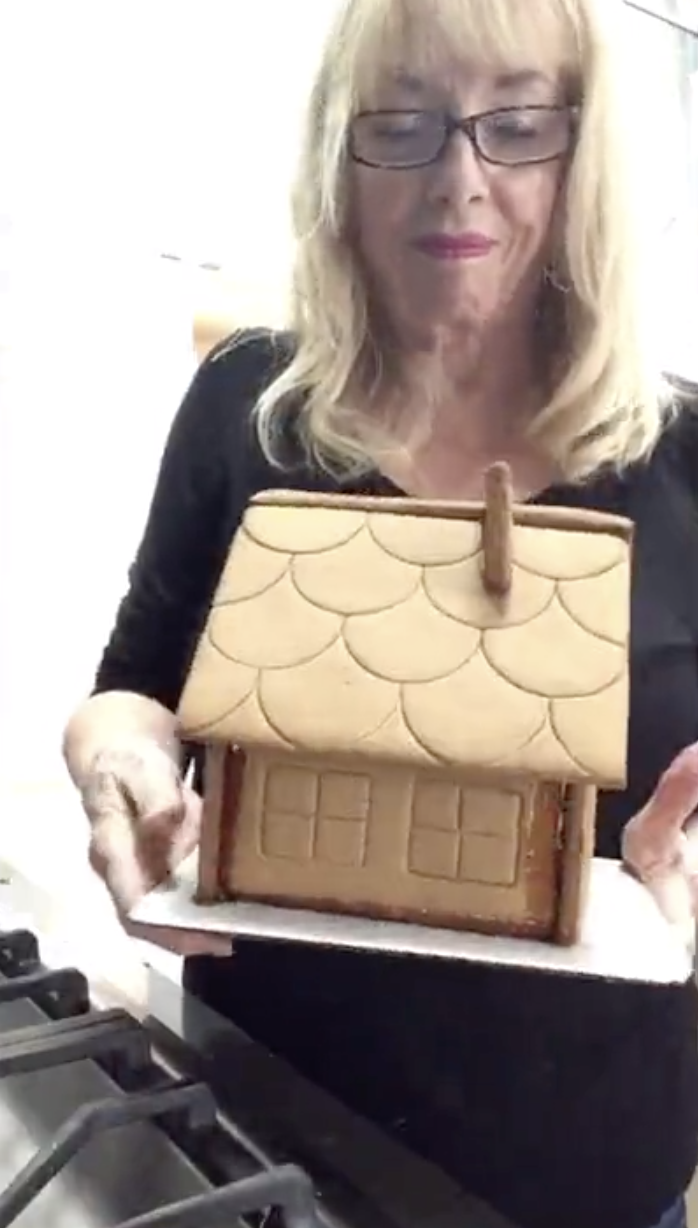 Anita holding her undecorated gingerbread house