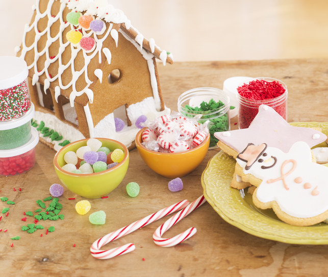 A gingerbread house decorated and held together with frosting surrounded by candy and snowman-shaped cookies