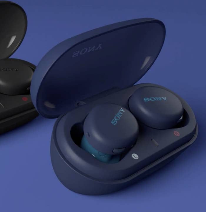 The dark blue earbuds in their charging case