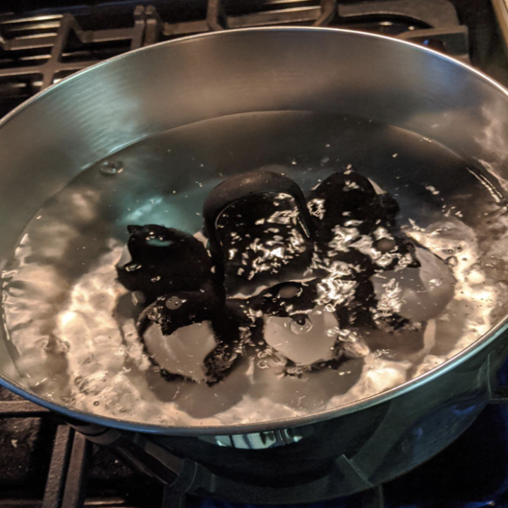 The penguin egg cooker submerged in boiling water