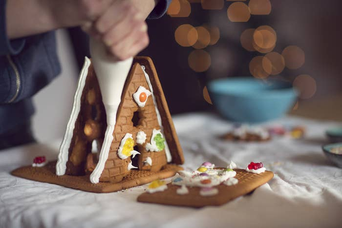 A person trying to put together a small gingerbread house
