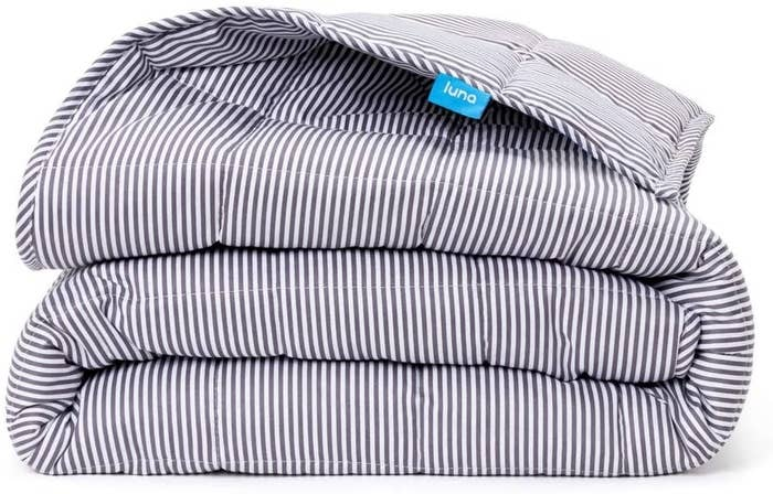 A folded blanket in striped white/grey
